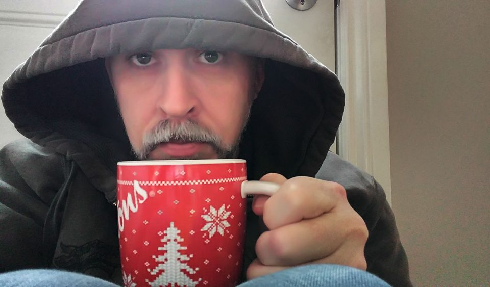 Hooded anxious man holding coffee mug