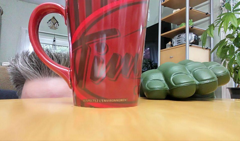 Hiding behind a coffee mug
