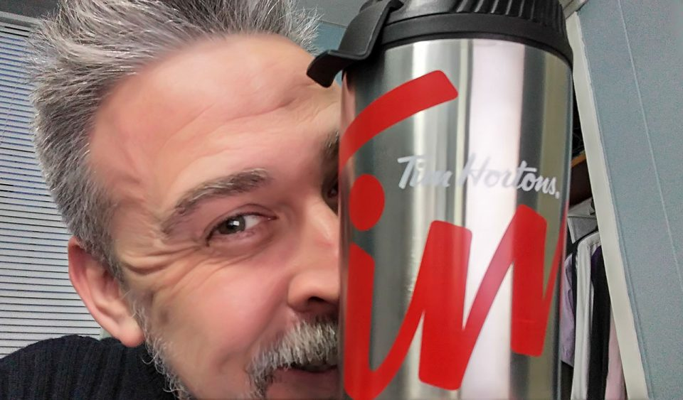 Peeking out from behind a coffee thermos